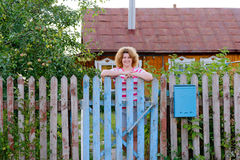 Middle-aged woman stands at the gates country Stock Photography