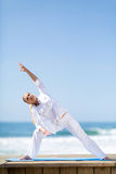 Middle aged woman stretching beach Stock Images