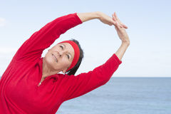 Middle aged woman stretching exercise ocean Royalty Free Stock Photography