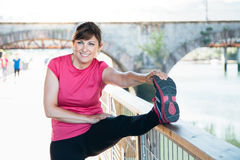 Middle aged woman stretching legs on a trail royalty free stock photos