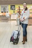 A middle-aged woman with a suitcase in a supermarket.  Royalty Free Stock Image