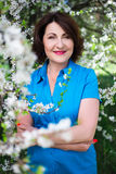 Middle aged woman in summer garden Royalty Free Stock Photography