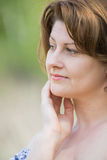 Middle-aged woman in the summer park. A stylish middle-aged woman in the summer park stock images