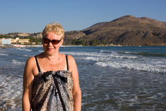 Middle-aged woman in sunglasses and sarongs. On the background of the Aegean Sea in Georgioupolis, Crete, Greece Stock Photos