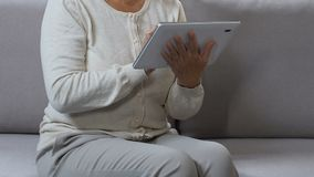 Middle-aged woman surfing web on tablet, shopping online, searching discount. Stock footage stock video