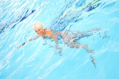 Middle-aged woman swimming. In the pool with blue water Stock Photography