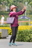 Middle-aged woman takes selfie in a park, Beijing, China. BEIJING-APRIL 28, 2016. Woman takes selfie with her smart phone. China mobile market will exceed US$717 royalty free stock images