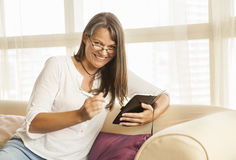 Middle aged woman taking notes. Middle aged woman wearing glasses, smiling and taking notes Stock Images