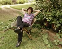 Middle-aged Woman Taking A Rest In Wheelbarrow. A middle-aged woman takes a rest in the wheelbarrow she has used to collect cuttings in her garden Stock Photo