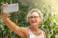 Middle aged woman taking self stock photo