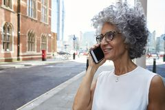 Middle aged woman talking on phone in city street, close up stock photo