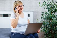 A middle-aged woman talking on the phone and working on laptop at home. royalty free stock photos