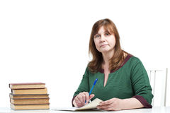 Middle-aged woman teacher checks the notebook. Royalty Free Stock Photo
