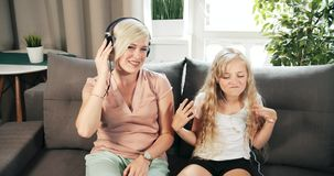 Mother and daughter listening to music. Middle-aged woman and teenage girl having fun together, listening to favorite soman and making dancing movements while stock video footage