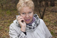 A middle-aged woman with telephone. In autumn forest Stock Photo