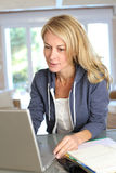 Middle-aged woman teleworking on laptop Royalty Free Stock Image