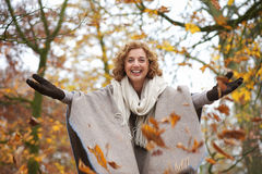 Middle Aged Woman Throwing Leaves Stock Images