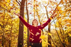 Middle-aged woman throwing leaves in the forest royalty free stock images