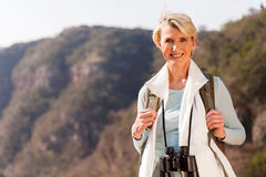 Middle aged woman top. Beautiful middle aged woman on top of the mountain with binoculars Stock Photos
