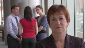 Middle aged woman - unhappy. A business woman in her late 50's looks into the camera while her coworkers talk in the background.  She appears to be unhappy stock footage