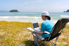 Middle-aged woman uses a laptop while on the beach Stock Image