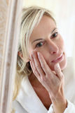 Middle-aged woman using daily cream Royalty Free Stock Images