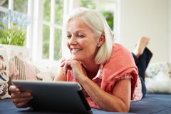 Middle Aged Woman Using Digital Tablet Lying On Sofa stock photos
