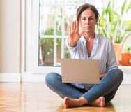 Beautiful middle age woman at home. Middle aged woman using laptop at home with open hand doing stop sign with serious and confident expression, defense gesture royalty free stock image