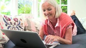Middle Aged Woman Using Laptop Lying On Sofa stock footage