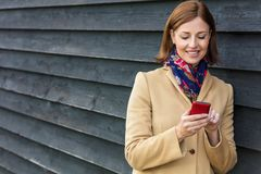 Middle Aged Woman Using Mobile Cell Phone. Attractive, successful and happy middle aged woman female using mobile cell phone for texting or social media Royalty Free Stock Photography