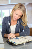 Middle-aged woman using smartphone and agenda Stock Photos