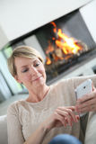 Middle-aged woman using smartphone by fireplace Stock Photography