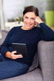 Middle aged woman. Using tablet computer at home Stock Photography