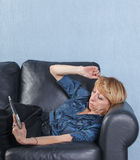 Middle aged woman using tablet PC on couch Royalty Free Stock Photography