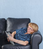 Middle aged woman using tablet PC on couch Royalty Free Stock Photos