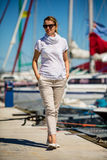Middle-aged woman on vacation walking in marina Stock Photo