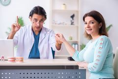 Middle-aged woman visiting male doctor stomatologist. The middle-aged women visiting male doctor stomatologist stock photo