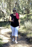 Middle-aged Woman Walking Along Track. A middle-aged woman exercises as she walks along a bush track stock photos