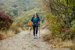 Middle-aged woman with walking poles traveling in rainy weather on mountain trail. Yalta, Russia - October 8, 2016: middle-aged woman with walking poles royalty free stock photo
