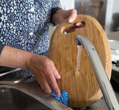 Middle-aged Woman Washing a Wooden Chopping Board. Royalty Free Stock Photos