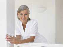 Middle Aged Woman With Water Glass On Verandah Stock Photos