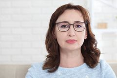 A middle aged woman wearing glasses looks kindly at the camera while sitting at home on the couch royalty free stock photo