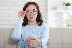 A middle aged woman wearing glasses looks kindly at the camera while sitting at home on the couch royalty free stock photos