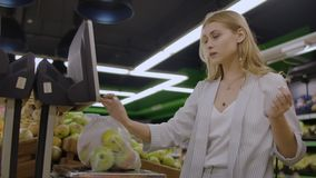 Middle-aged woman weighs a bag of apples in the supermarket. stock video footage