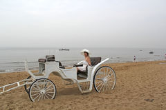 Middle-aged woman in a white dress and a hat in a white open carriage on a background of the sea coast. Middle-aged woman in a white dress and a big white hat in Royalty Free Stock Photos