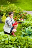 Middle-aged woman working in a flower garden. Beautiful middle-aged woman working in a flower garden stock photo
