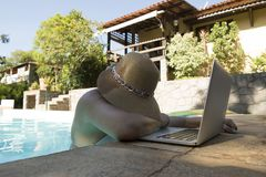 middle-aged woman working on the laptop inside the pool on very hot summer day stock image