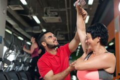 Middle aged woman working out with coach in gym. Middle aged female client working out with dumbbells. Young male fitness coach assisting brunette women in gym Royalty Free Stock Image