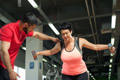 Middle aged woman working out with personal coach Stock Photos