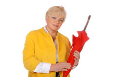 Middle-aged woman in a yellow jacket with a red umbrella Royalty Free Stock Photos